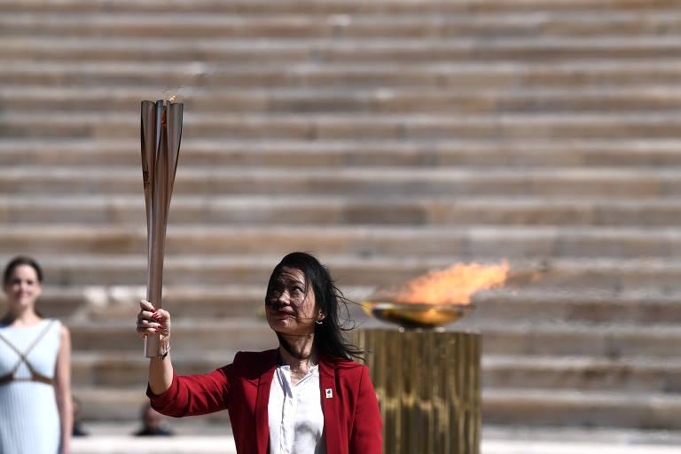 A ex-nadadora japonesa Imoto Naoko ergue a tocha e olha para ela no estádio Panatenaico