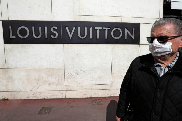 Homem usa máscara ao lado de uma loja da Louis Vuitton