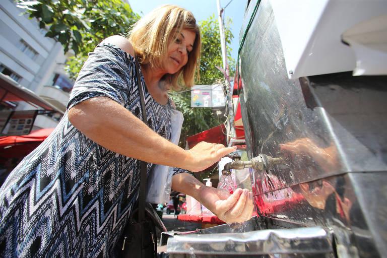Os feirantes da feira livre da praça da Liberdade colocam lavatório com detergente e álcool em gel para os clientes, a nova rotina dos brasileiros