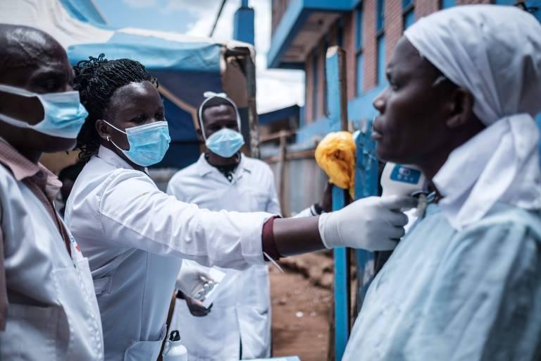Médica negra está do lado esquerdo da fotos, acompanhada de dois colegas e coloca o termômetro no pescoço de uma paciente. Todos estão de jalecos brancos, lucas brancas e máscaras azuis.