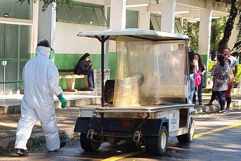 Funcionário vestido com veste de proteção branca e luvas caminha no cemitério perto de um carrinho que leva um caixão