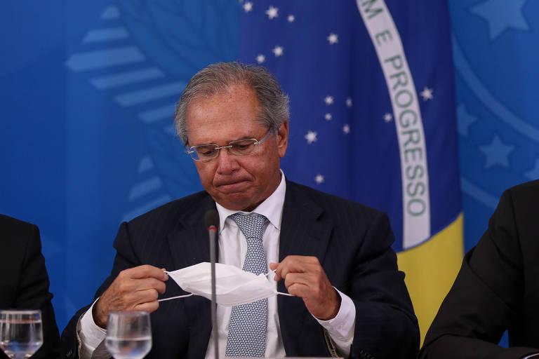 Ministro da Economia, Paulo Guedes, manipula uma máscara descartável em meio a uma entrevista com jornalistas para falar sobre medidas do governo para controlar a pandemia de coronavírus