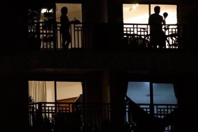 Moradores de prédio residencial aparecem nas janelas batendo panelas