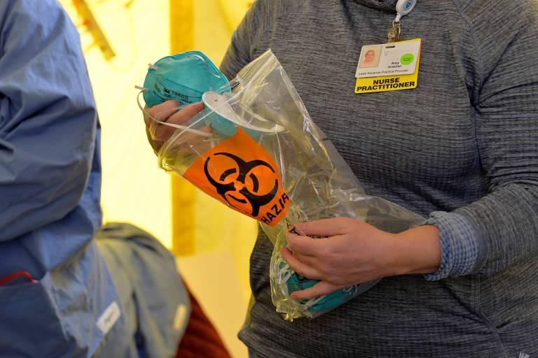 Enfermeira segura equipamento de proteção antes de realizar teste em hospital de Massachusetts