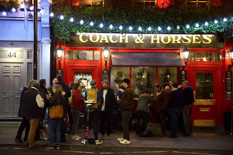 Vários jovens na calçada em frente à fachada do pub Coach & Horses, que tem portas vermelhas