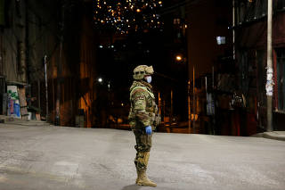 A Bolivian military officer stands on a street in the empty city centre of La Paz