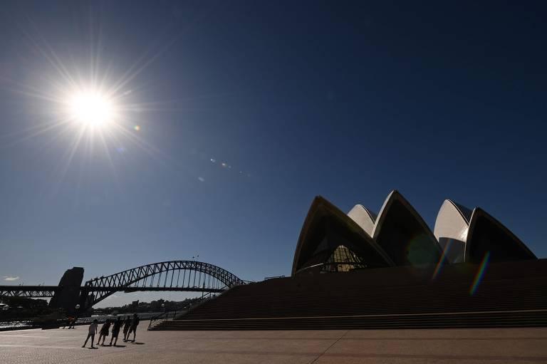 Grupo de turistas caminha em frente à Ópera de Sidney um dia após a Austrália anunciar o fechamento das fronteiras na esperança de conter a Covid-19