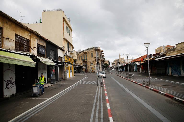 Trabalhador em Tel Aviv, Israel, caminha pela rua vazia; país aprovou política nacional de quarentena após a disseminação da Covid-19