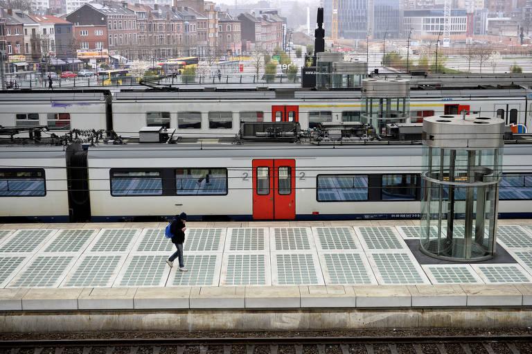 Homem atravessa a estação ferroviária quase vazia em Liège, na Bélgica, depois que o país impôs um bloqueio para diminuir a propagação do novo coronavírus