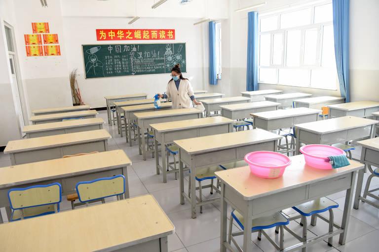 Professora higieniza sala de aula de uma escola secundária no condado de Yecheng, noroeste da China