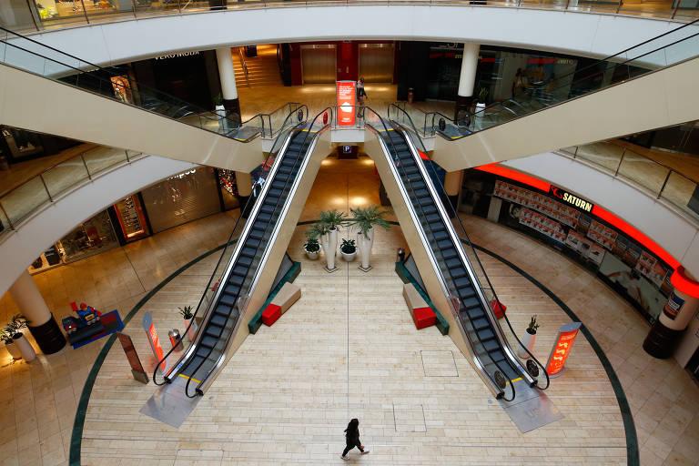 Mulher caminha dentro de shopping vazio durante um bloqueio parcial em Leverkusen, na Alemanha