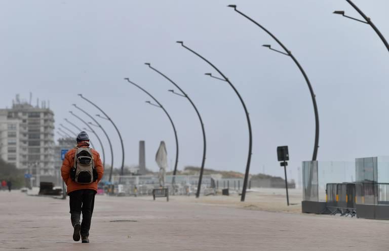 Homem caminha no calçadão deserto da cidade de Koksijde, na Bélgica