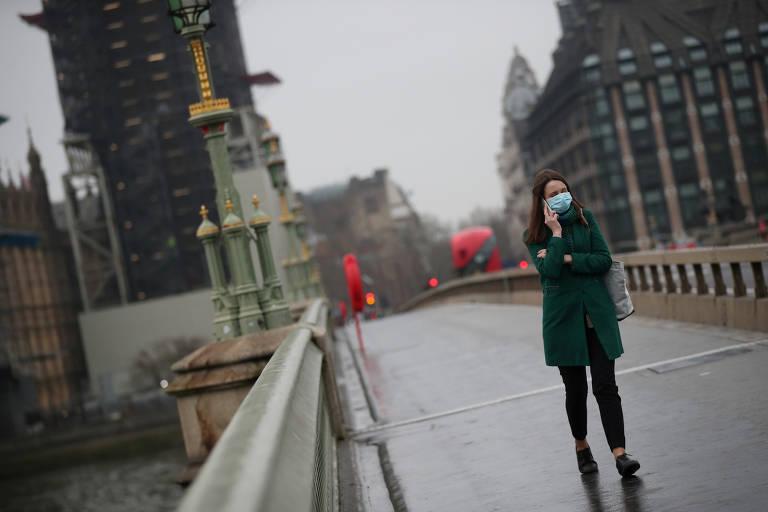 Mulher com máscara de proteção caminha na ponte de Westminster, em Londres, Reino Unido