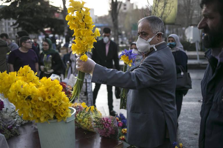 Homem compra flores para celebração de Ano-Novo em mercado de Teerã