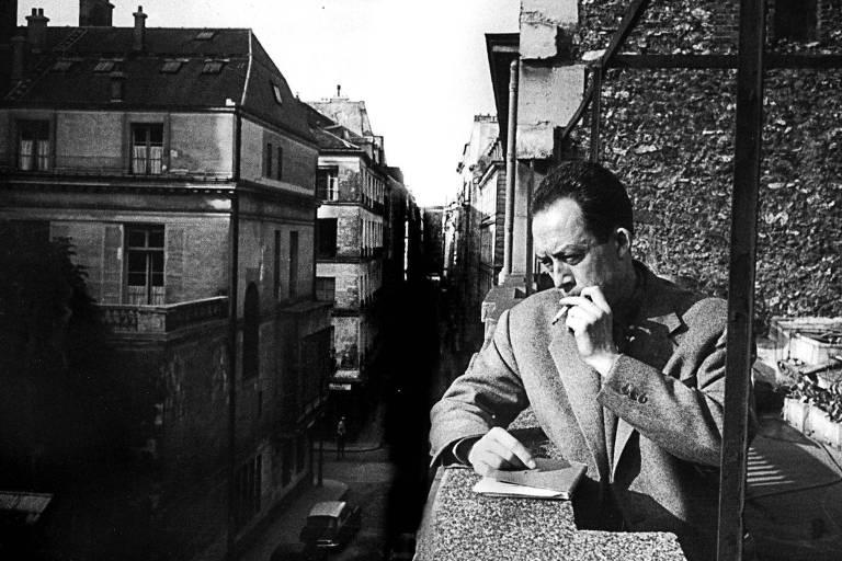 """francês Albert Camus fuma na sacada da editora pela qual publicou """"A Peste"""""""