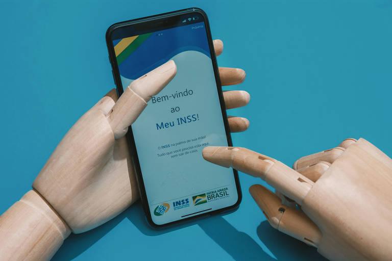 Mão de madeira segura celular, que está com o aplicativo Meu INSS em funcionamento
