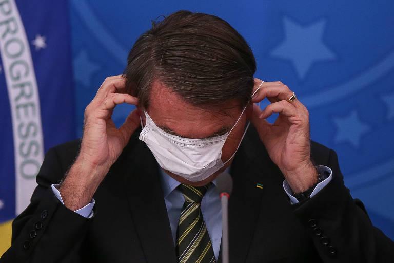 O presidente Jair Bolsonaro, durante entrevista à imprensa na qual ele e vários ministros se apresentaram usando máscaras descartáveis de forma errônea; na foto, Bolsonaro se atrapalha, puxando a máscara para o alto da cabeça, de modo que lhe tampa os olhos