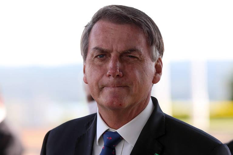 A foto mostra o presidente Jair Bolsonaro dos ombros para cima. Ele tem uma expressão de como estivesse prestando atenção em algo que alguém estivesse falando com ele.
