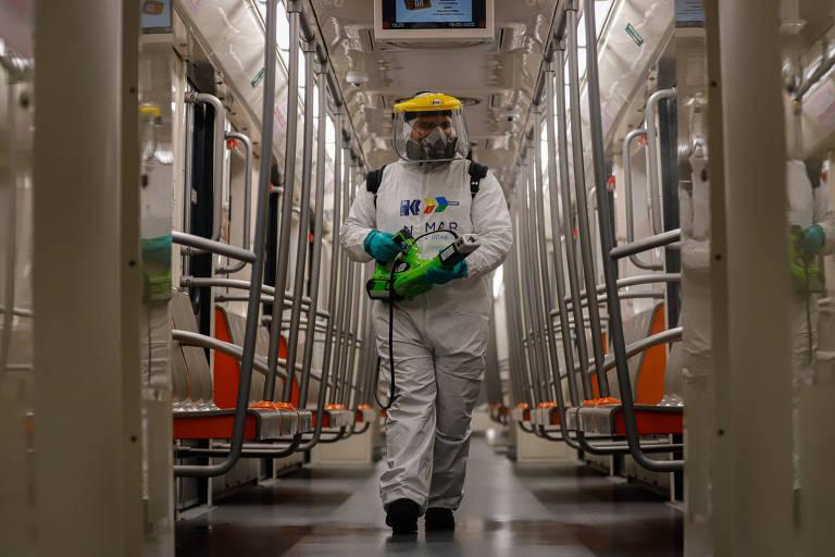 Um trabalhador sanitiza um vagão de metrô