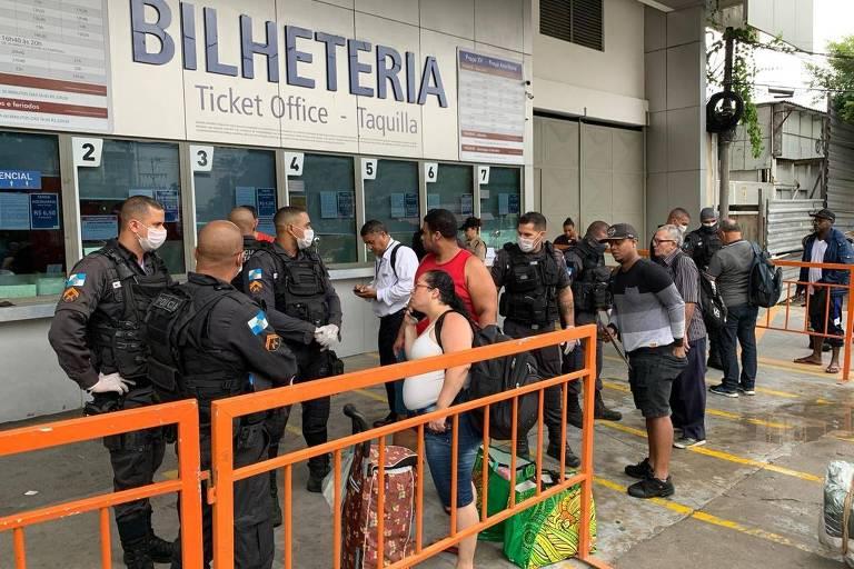 Pessoas em Niterói conversam com a polícia, vestida de preto, em frente às bilheterias das barcas