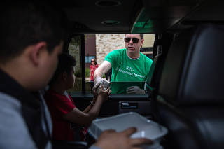 Joe Chandler, the principal at Brenham High School, hands out meals to families at a drive-thru at Alton Elementary School, in Brenham, Texas, on March 17, 2020. (Tamir Kalifa/The New York Times)