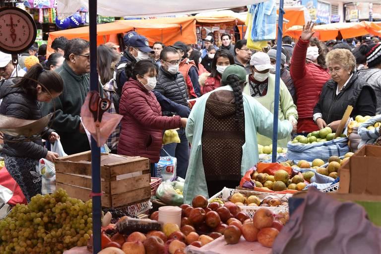 Bolivianos vão a mercado de rua em La Paz usando máscaras no dia em que a presidente interina, Jeanine Añez, decretou quarentena a partir deste domingo (22)