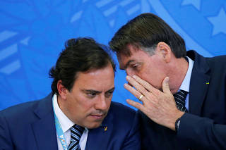 Brazil's President Jair Bolsonaro talks with Caixa Economica Federal bank President Pedro Guimaraes during a launch ceremony of real estate credit incentive program of the Caixa Economica Federal Bank at the Planalto Palace in Brasilia