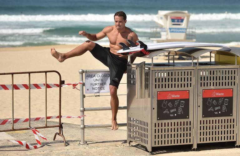 Imagem mostra homem sem camisa com uma prancha pulando barreira de metal no meio de uma praia. Ao fundo é possível ver o mar