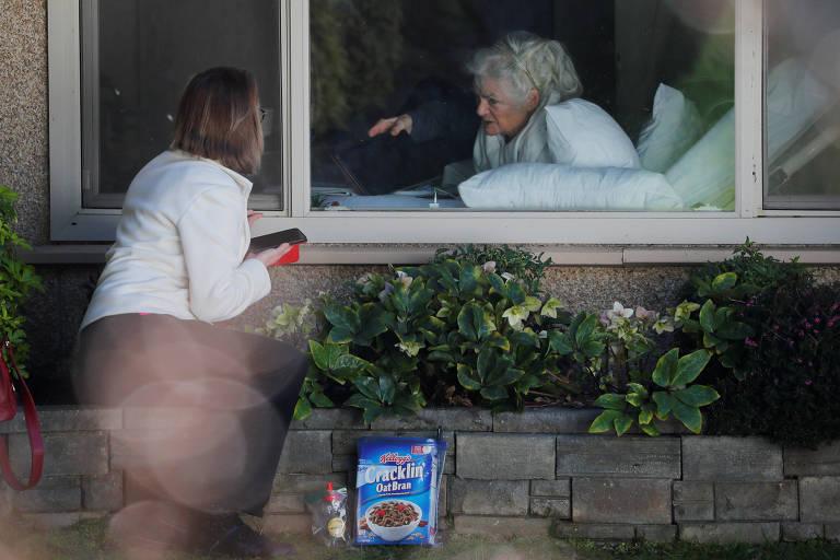 mulher conversa com mãe através da janela