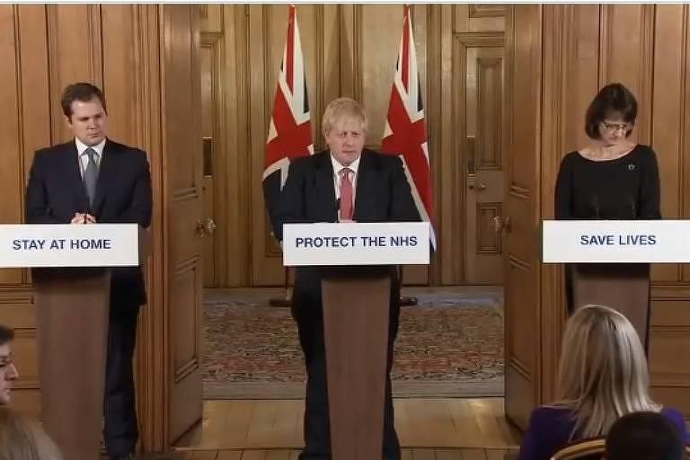 O primeiro-ministro britânico, Boris Johnson (centro), adotou cartazes com frases curtas e diretas que tem usado em seus pronunicamentos: fique em casa (em frente ao secretário de comunidades, Robert Jenrick, esq.); projeta o sistema de saúde, em frente a Boris, e salve vidas, em frente à responsável-adjunta de saúde, Jenny Harries, dir.