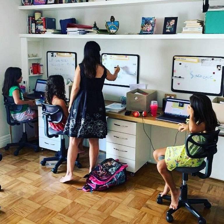 Mãe ajuda filhas trigêmeas a estudarem em casa durante suspensão das aulas em razão da pandemia de coronavírus