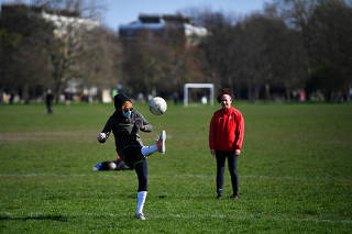 A woman wearing a mask plays football on Clapham Common in London