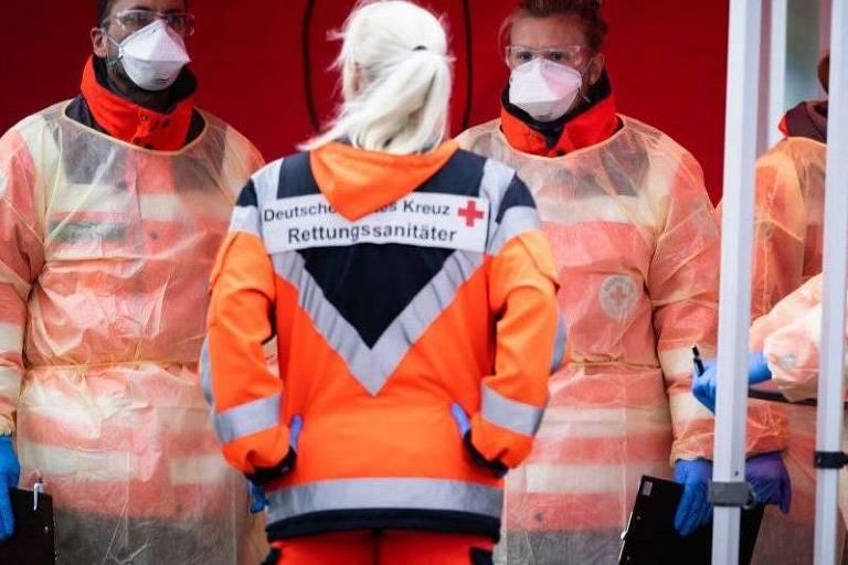 Agentes de saúde vestidos com roupa laranja