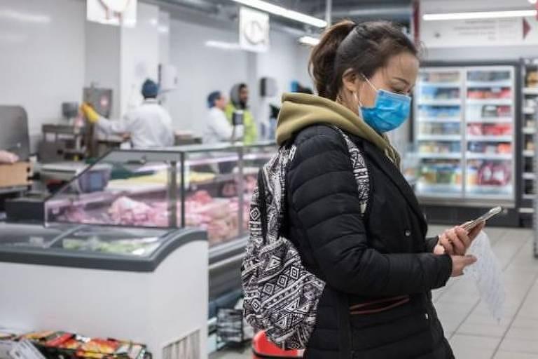 De máscara, mulher mexe no celular em loja de conveniência