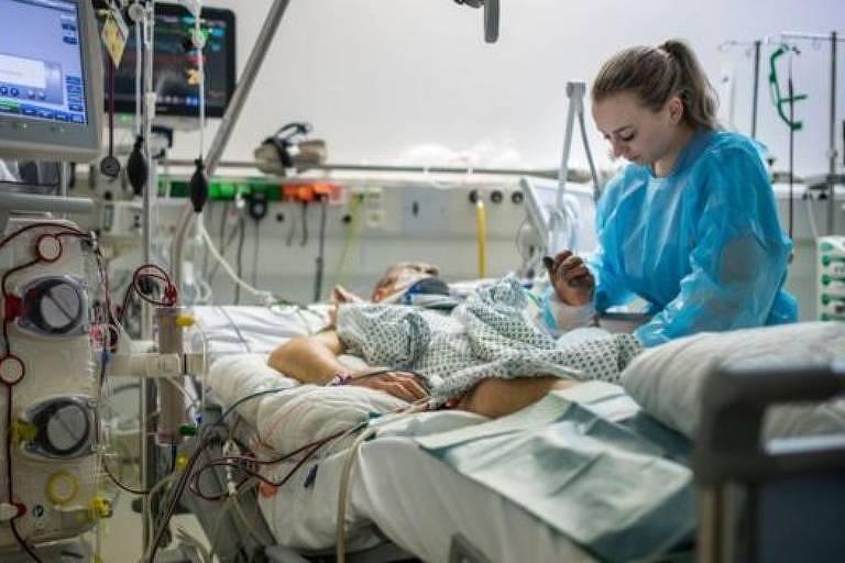De avental azul, médica trata paciente acamado