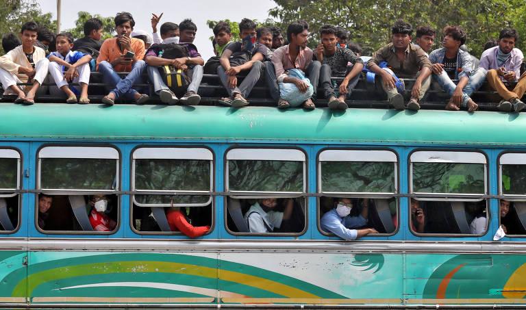 ônibus verde trafega lotado, com pessoas sentadas no seu interior e várias outras sobre o teto do veículo