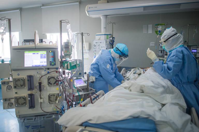 Médicos atendem paciente infectado pelo novo coronavírus em hospital em Wuhan, na China