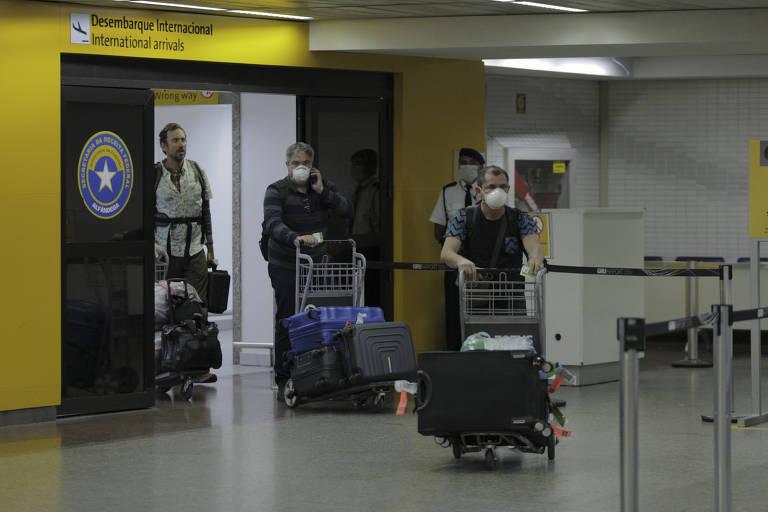 Homens com máscara cirúrgica empurram carrinho com malas, em aeroporto