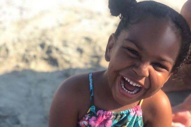 Menina de 4 anos chamada Catarina na praia. Usa duas chuquinhas altas na cabeça. Ela é negra com sorriso largo. Usa biquini florido