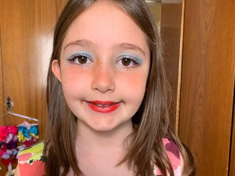 Júlia Coca, 8 anos, maquiada com batom vermelho, sobra azul com esfumaçado branco. Tem cabelo liso castanho pelos ombros, pele bem clara, bochechas rosa devido ao blush usado. Usa uma camiseta florida