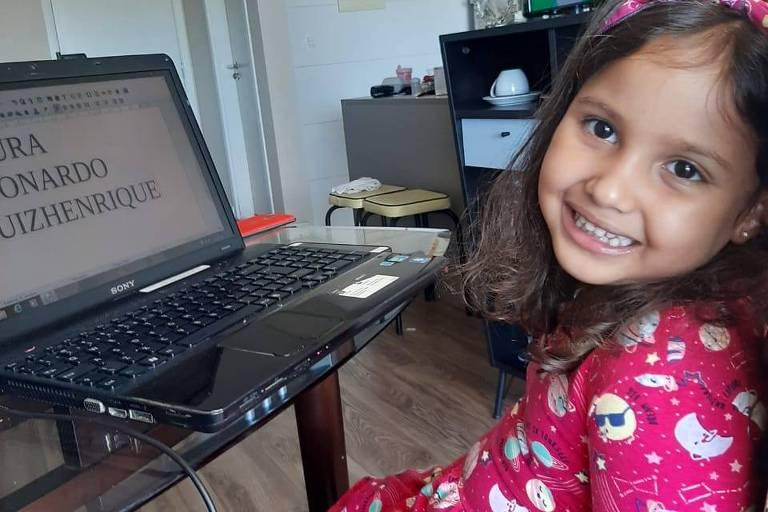 Pai em cadeira de rodas auxilia filha Elis, 4 anos, a fazer educação física em casa no confinamento causado pela prevenção ao corona vírus
