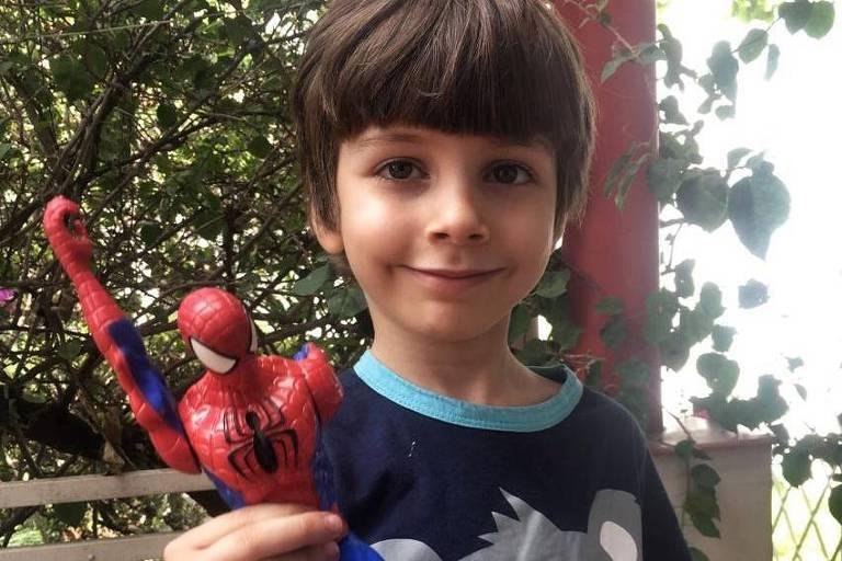 Felipe Peres Cruz, 5, com um boneco de homem-aranha em mãos sorri de boca fechada, usa cabelo tigelinha