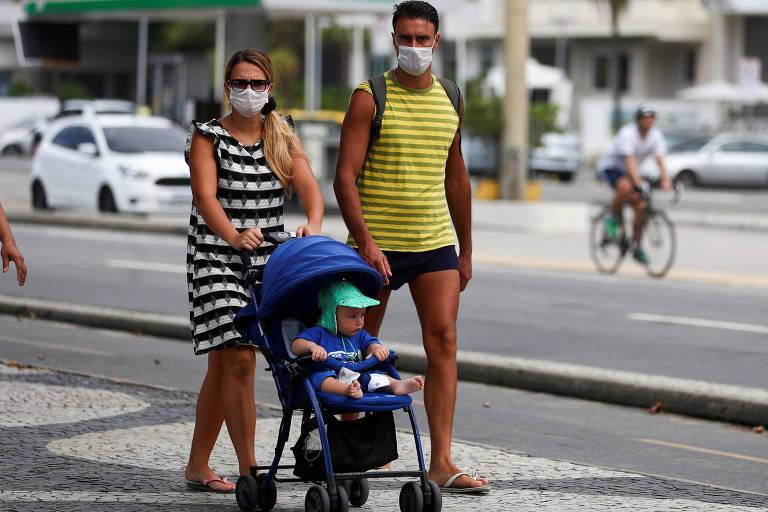 Casal com máscaras passeia com bebê na praia de Copacabana; a mulher está de vestido listrado branco e preto, o homem, de short e de camiseta regata amarela e preta, também listrada; ela empurra um carrinho azul no qual vai um bebê com chapéu verde