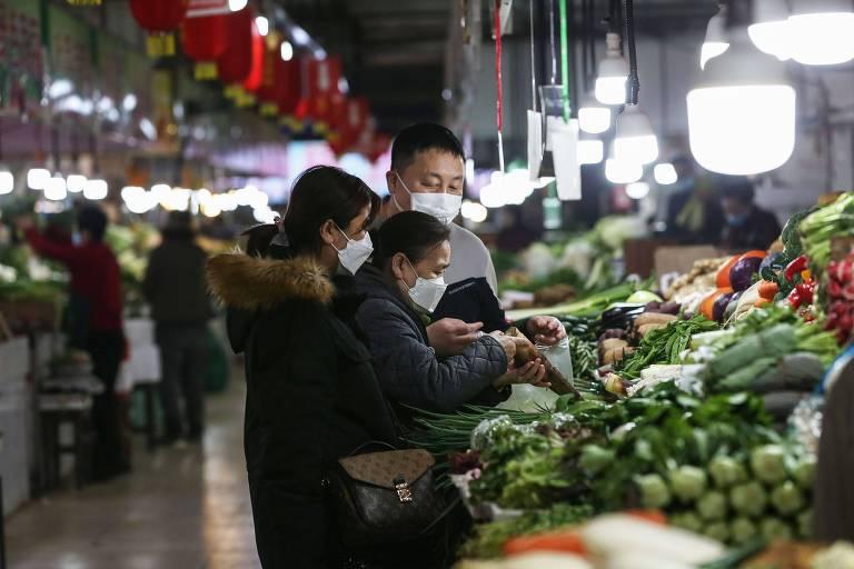 Consumidores compram vegetais em mercado na província de  Liaoning, na China
