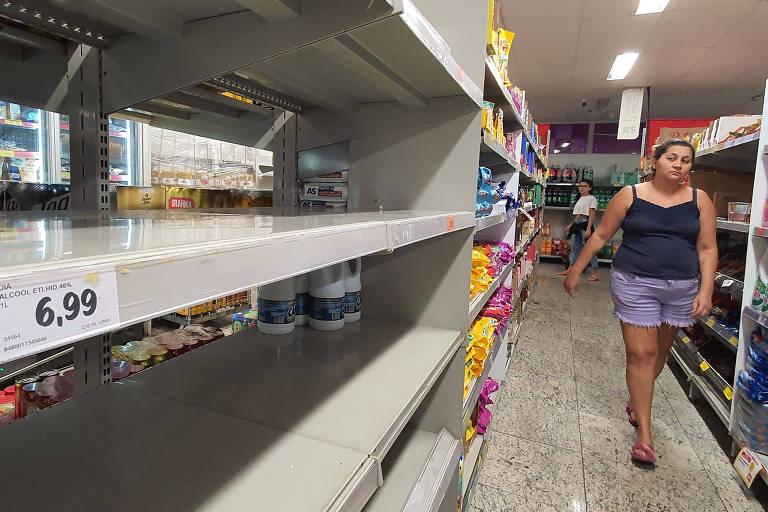 Mulher caminha em um corredor de supermercado com grande parte das prateleiras vazias