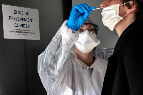 TOPSHOT - A person has a sample collected to be tested for COVID-19 on March 23, 2020, at the CBM69 laboratory, part of Eurofins clinical diagnostics group, in Villeurbanne, central-eastern France, on the seventh day of a lockdown aimed at curbing the spread of the COVID-19 (novel coronavirus) in France. (Photo by JEFF PACHOUD / AFP)
