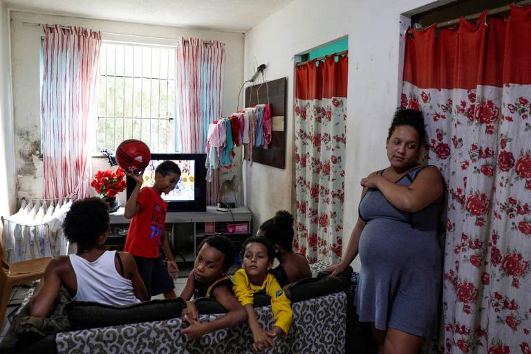 De pé, à direita, está Estela Rosa, apoiada num sofá de uma sala de estar com TV e cortinas, onde estão as outras cinco pessoas que moram com ela, sendo quatro crianças
