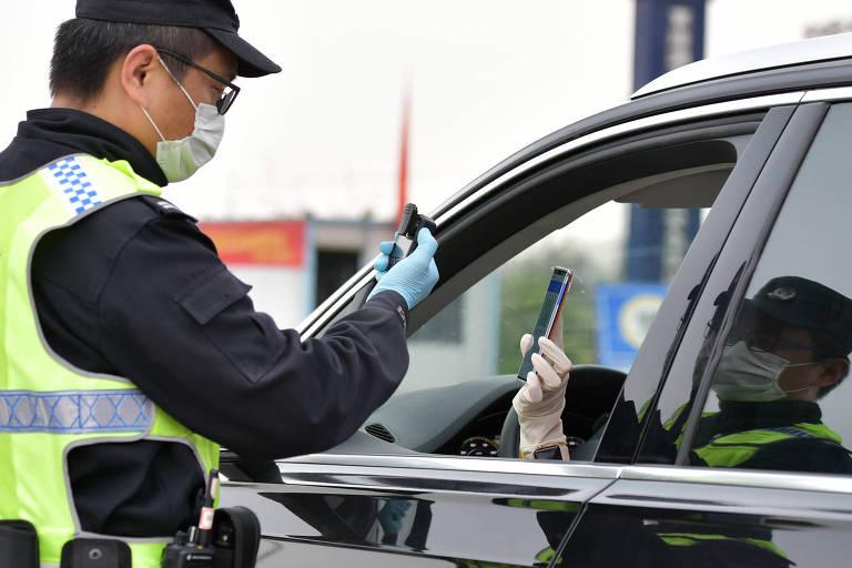 Agente confere código que mostra estado de saúde de habitante em rodovia em Wuhan, na próvíncia de Hubei