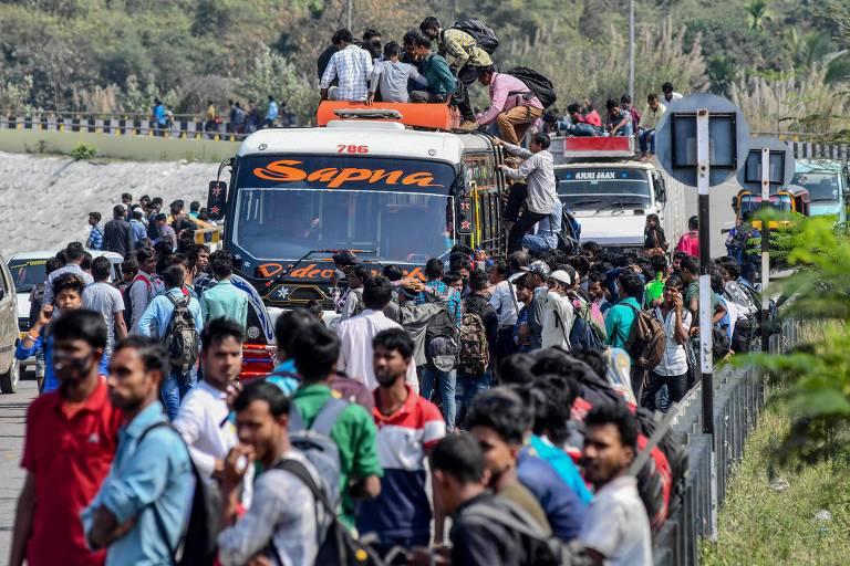 Multidão tenta pegar ônibus na cidade de Guwahati, na Índia, nesta terça (24), horas antes do governo anunciar o confinamento obrigatório