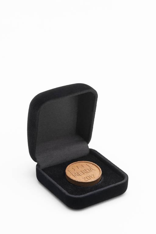 estojo de joias exibe uma moeda com a palavra 'merda' gravada